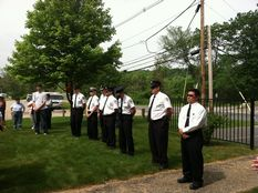 Adults standing in a row looking somberly ahead at Memorial Day ceremony
