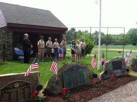 Boy Scouts anbd Girls scouts standing somberly behind and looking at memorial stones decorated with American flags