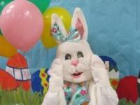 Person in Easter Bunny costume with large balloons in background